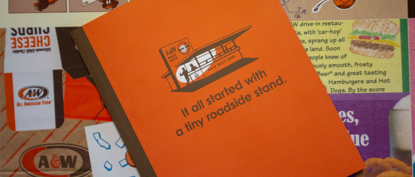 Front cover of A&W 100th Anniversary Book. Cover is orange with brown band on left side. Illustration on vintage A&W Root Beer stand is in the middle. Text below illustration reads