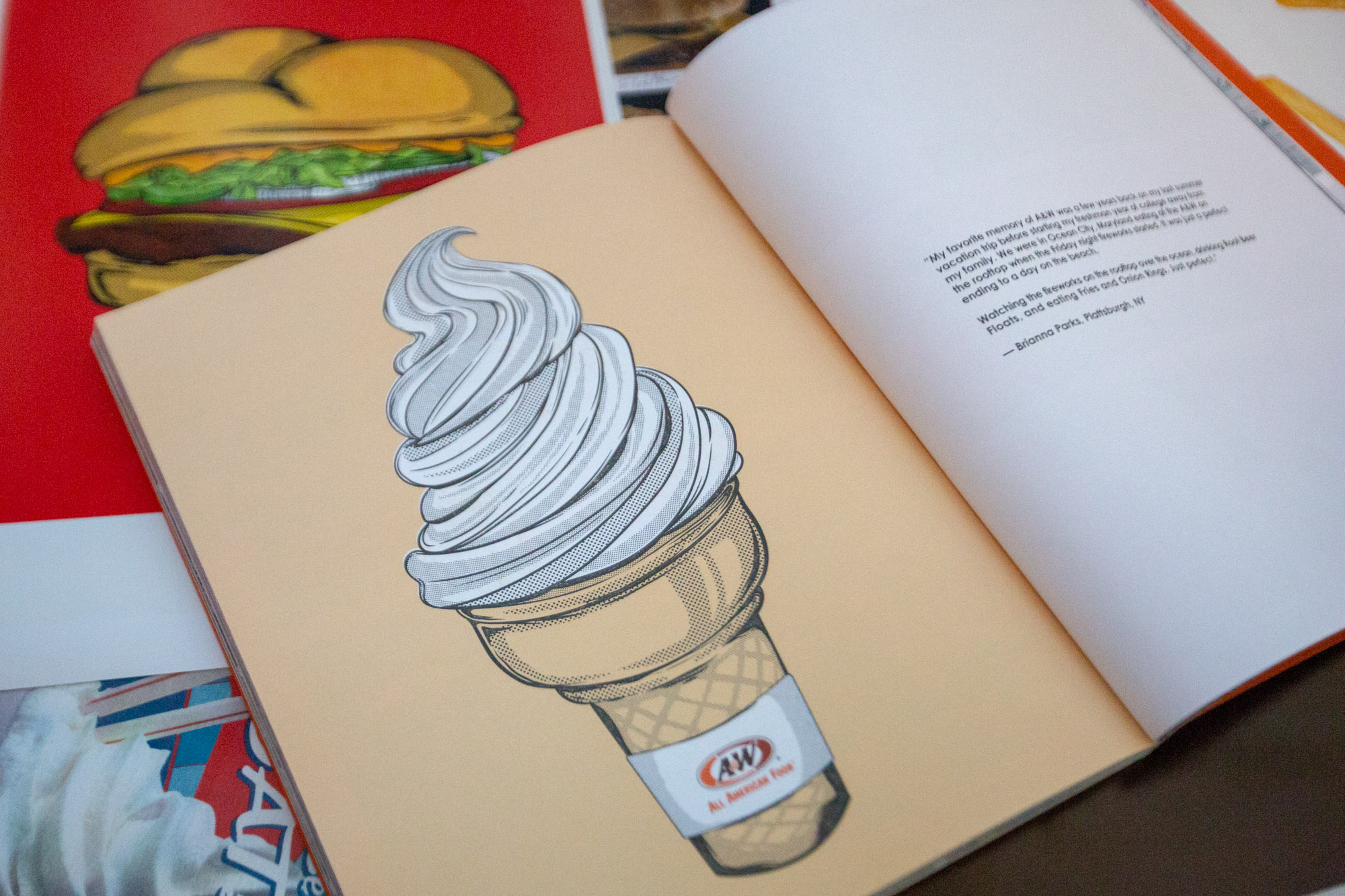 A&W 100th Anniversary Book with drawing of a vanilla soft serve cone on the left page, fan story on the right page.