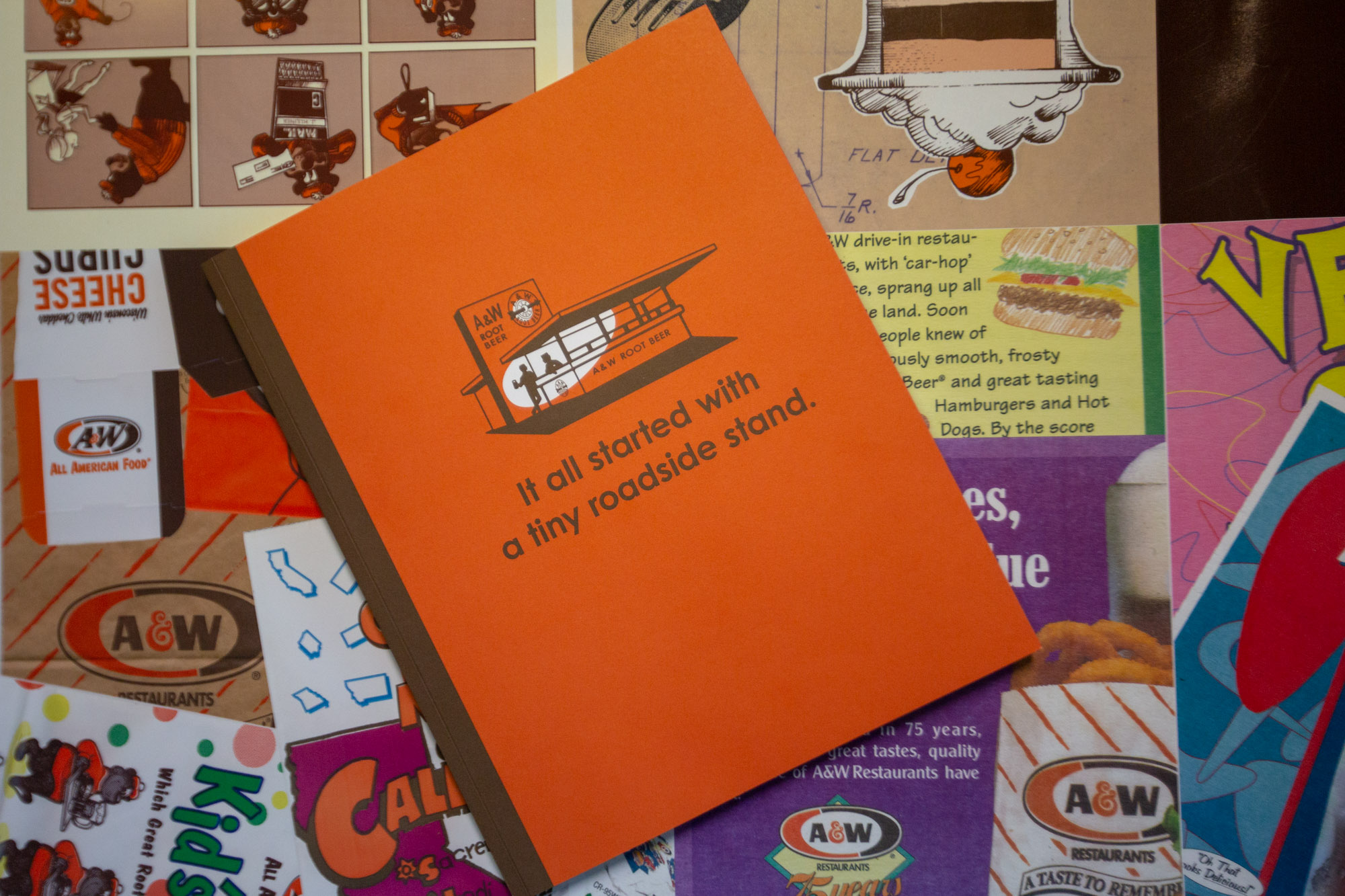 Overhead photo of A&W 100th Anniversary Book on collage background. Book is orange with illustration of A&W Root Beer Stand on the cover with text 'It all started with a roadside stand' below in brown.