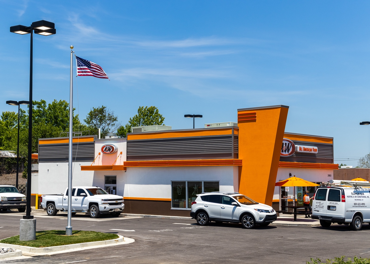 Exterior side view photo of A&W Restaurant showing cars in drive-thru and team member walking bag out to car.