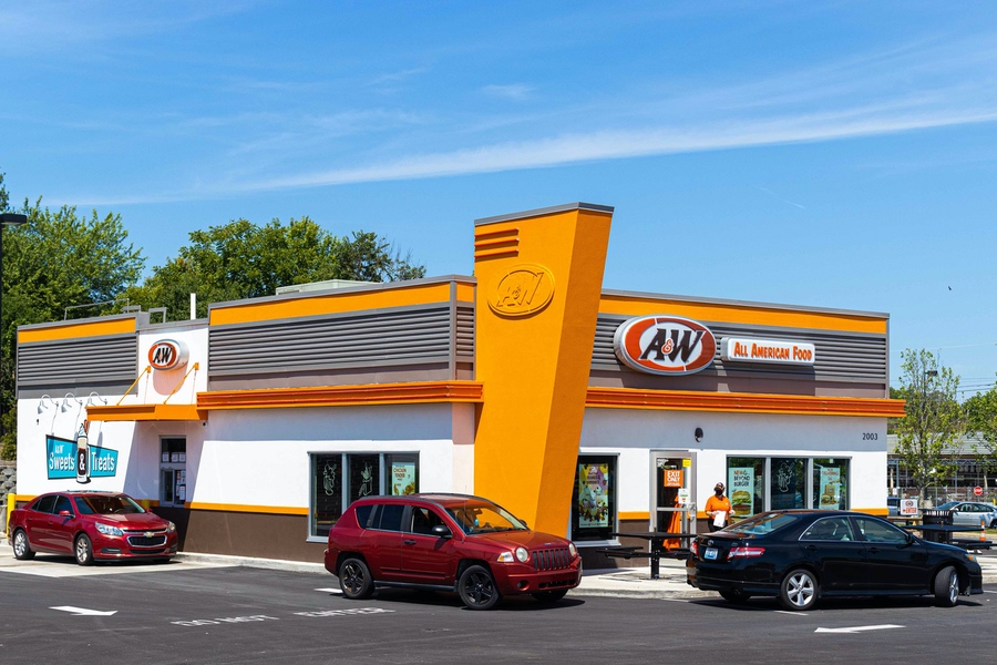 Exterior of A&W Restaurant in Richmond, Kentucky. Three cars are in the drive-thru. Team member is walking to a car holding an A&W to-go bag.