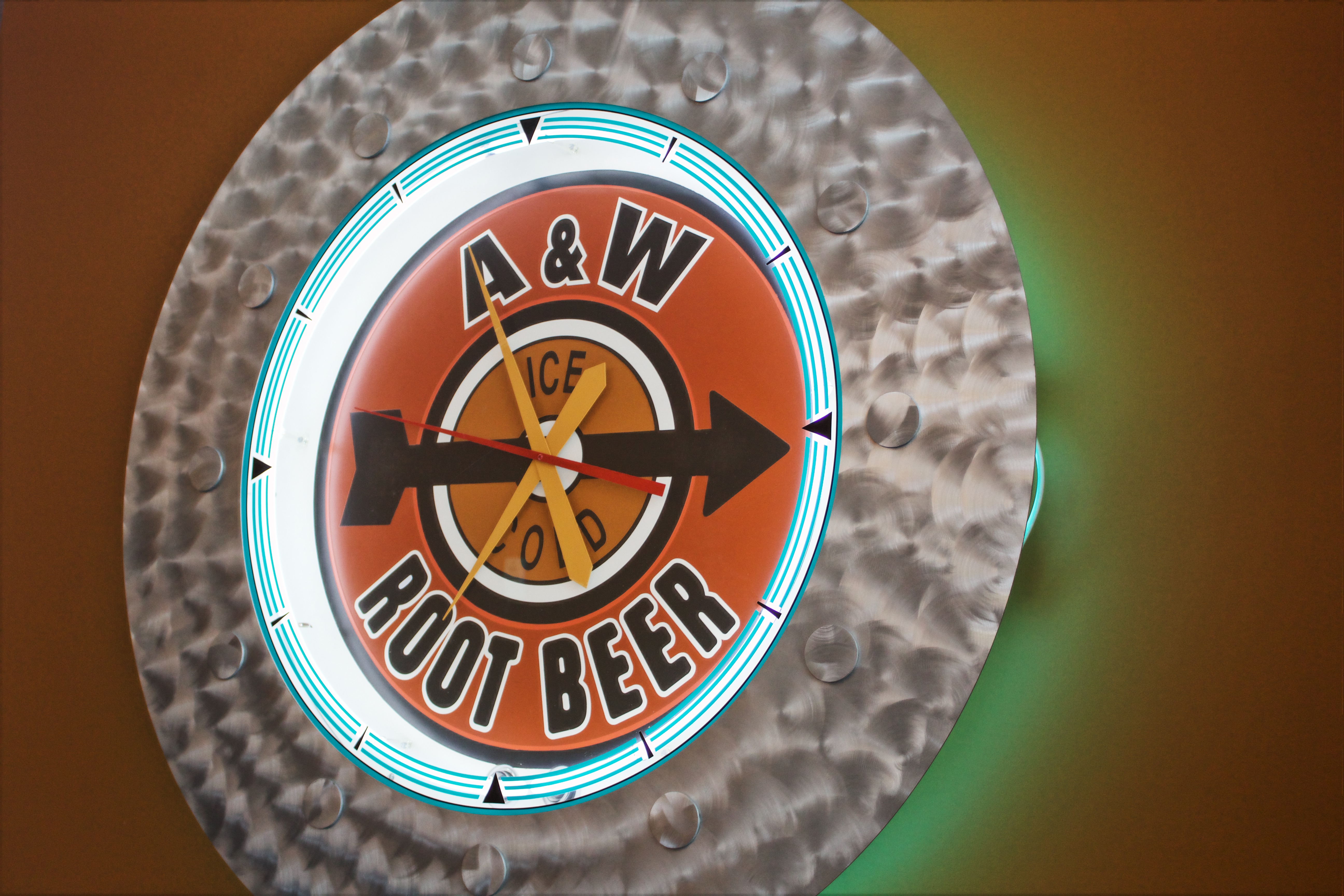 Round clock that reads 'A&W Root Beer' on an orange wall