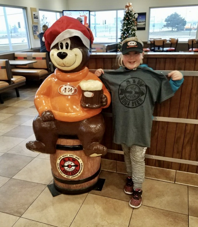 Photo of Abby holding a gray A&W t-shirt next to a statue of Rooty the Great Root Bear