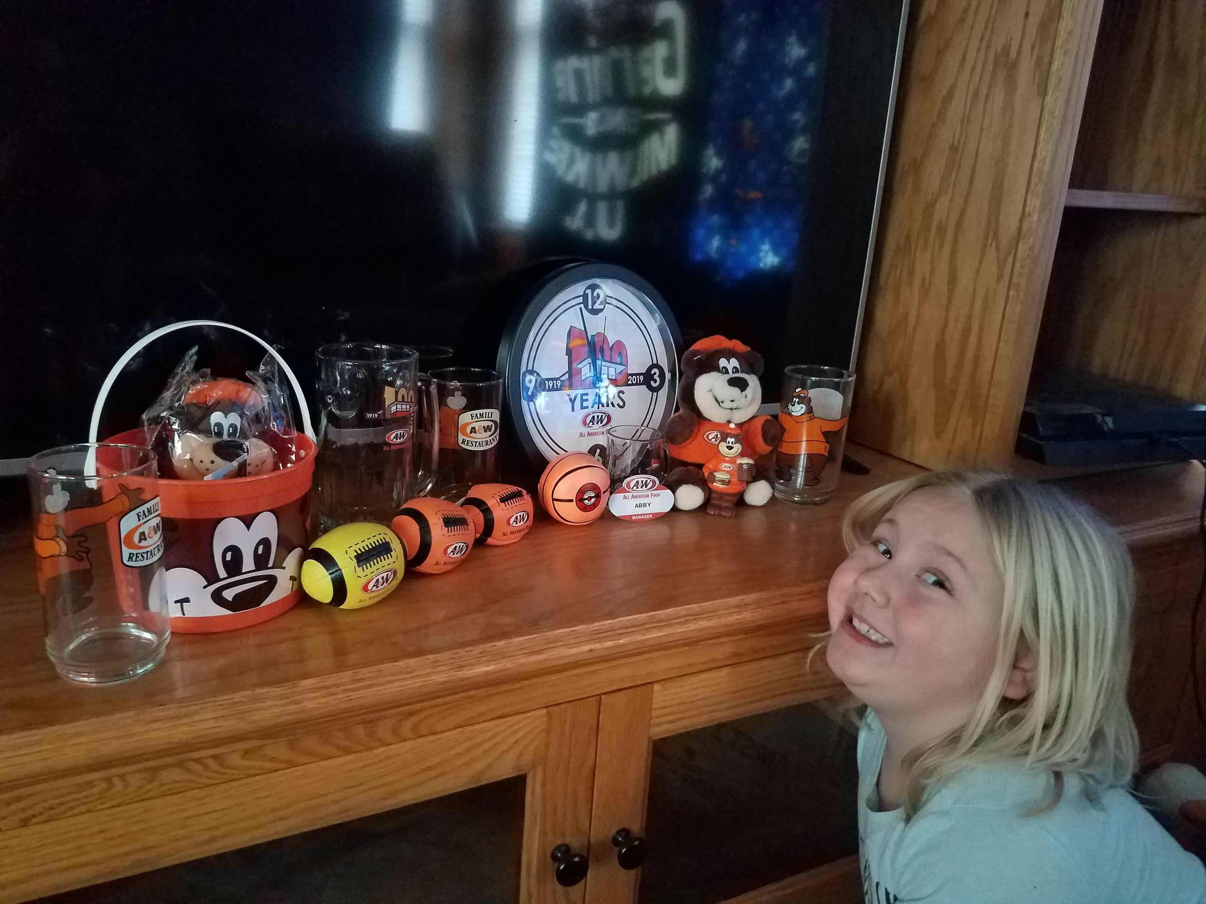 Photo of Abby sitting next to a shelf displaying various A&W Restaurants memorabilia