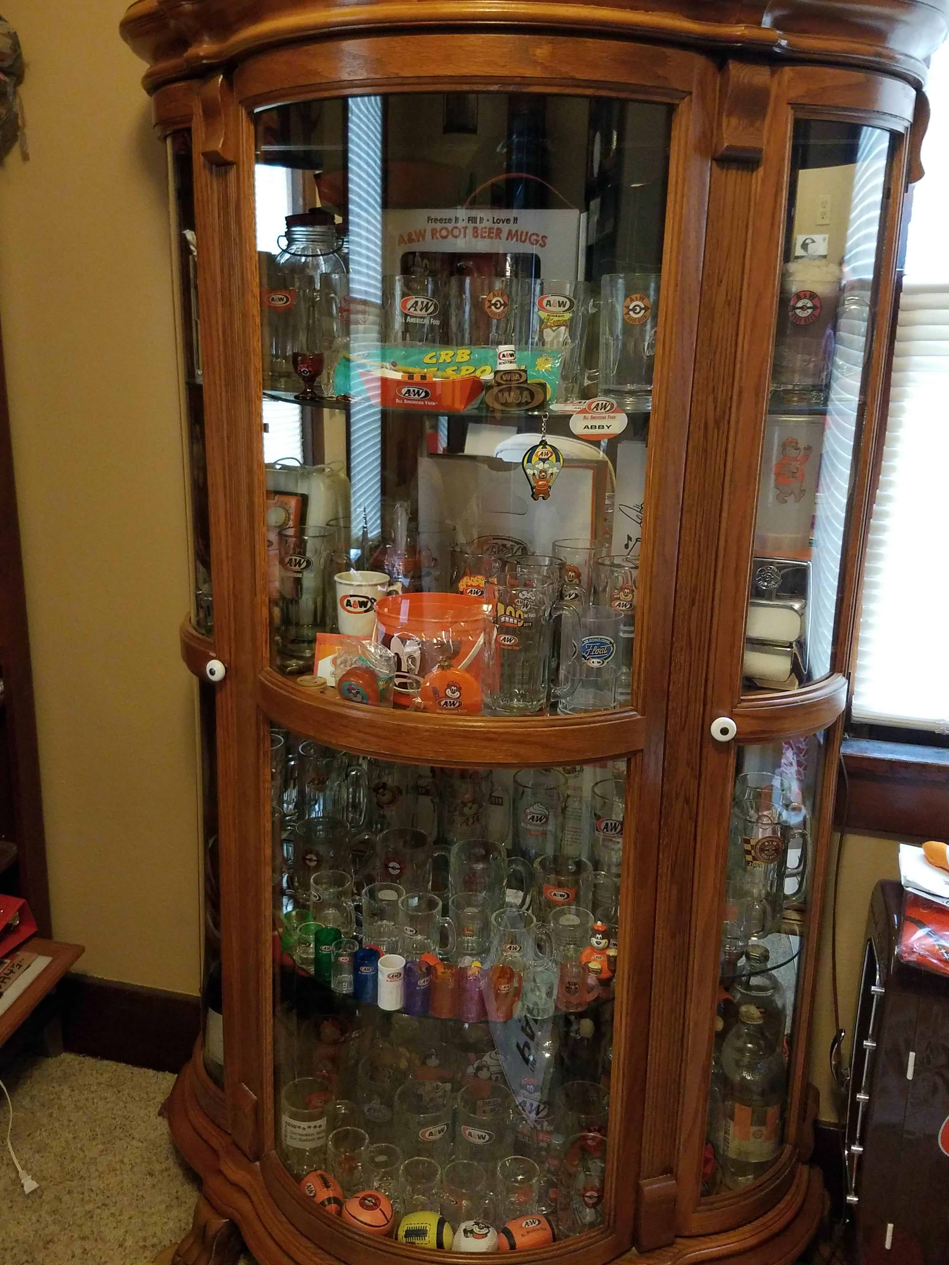 Photo of a display case containing various A&W Restaurants memorabilia and mugs.
