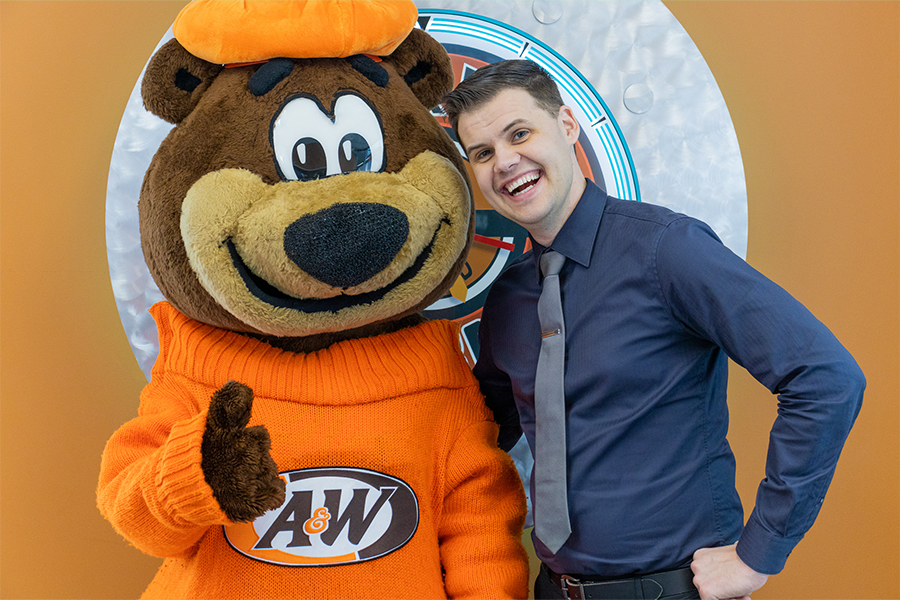 Photo of Brett Allan with Rooty the Great Root Bear.