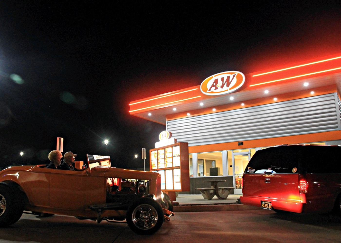 Two cars in A&W Restaurant drive-thru during the nighttime.