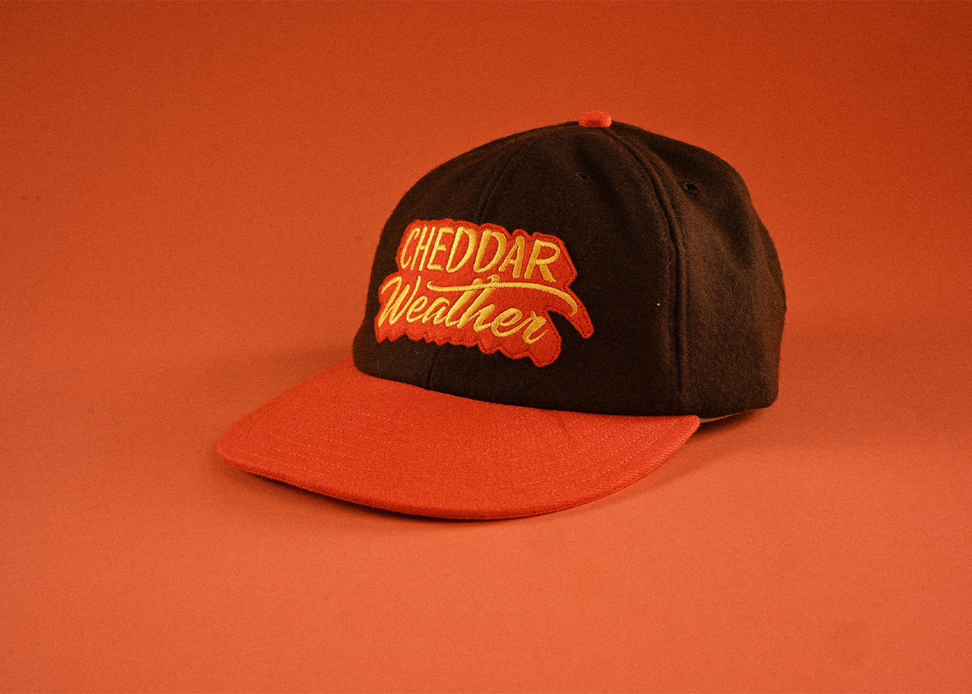 Cheddar Weather Baseball Cap on orange background.
