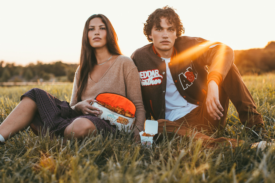 Photo of a woman and a man sitting together outside wearing Cheddar Weather merchandise.