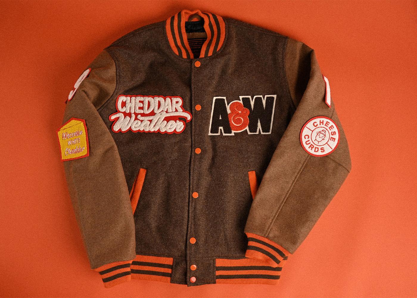 Cheddar Weather Letterman Jacket on orange background.