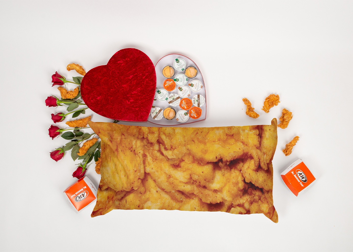 Flat lay photo of a body pillow that looks like an A&W Chicken Tender. The pillow is surrounded by a heart-shaped box filled with A&W sauces and Chicken Tenders.