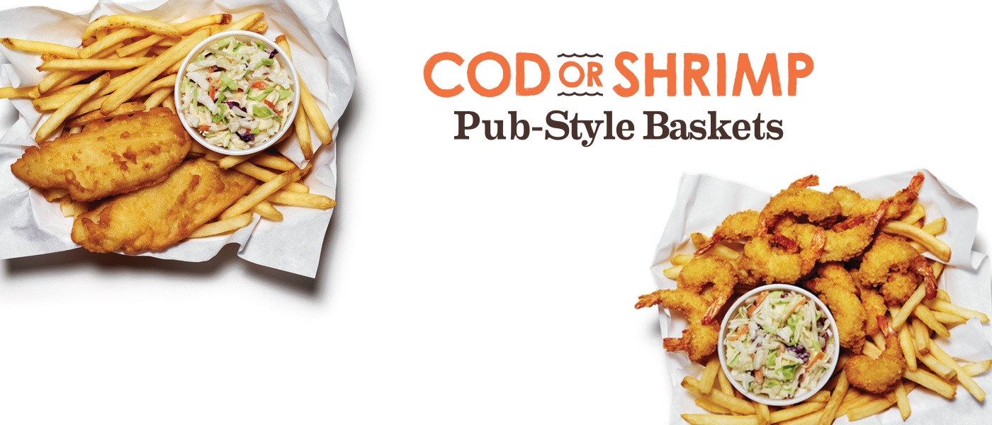 Two baskets - one with golden-fried shrimp and another with cod. Both with fries, and coleslaw