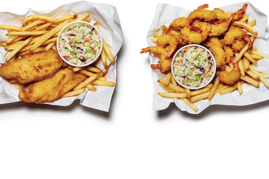 Overheard shot of two pub style baskets. One with cod, the other with shrimp. Both have fries and coleslaw.