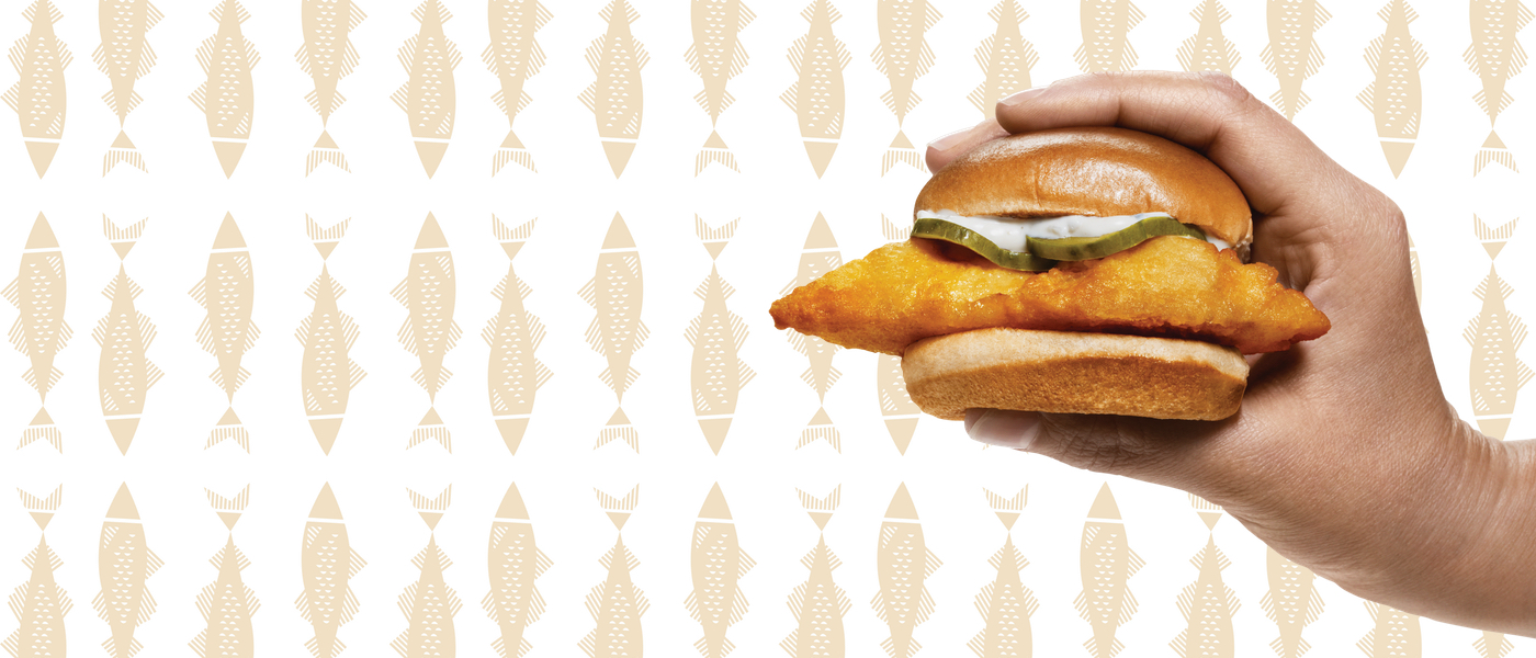 Background has drawings of fish. Person is holding a Cod Slider in their hand on the right side of the image.