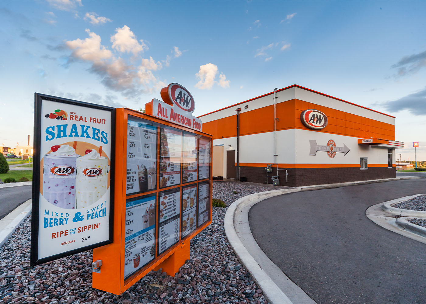 Exterior photo of A&W Restaurant drive-thru side during daytime.