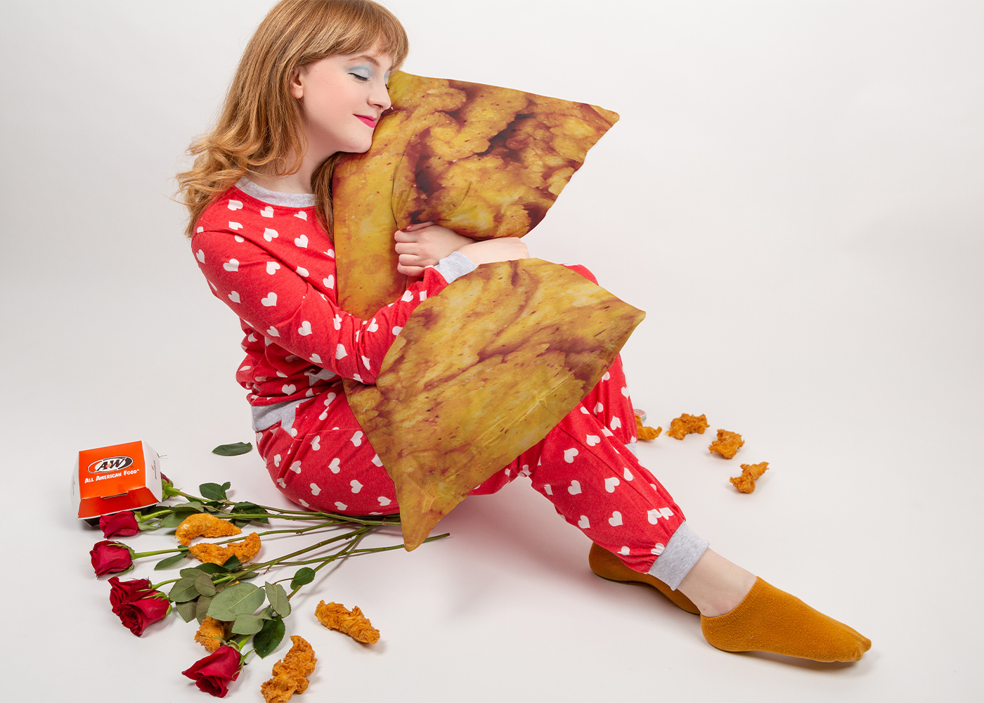 Girl wearing red heart pajamas is sitting on the floor. She is holding a body pillow that looks like an A&W Chicken Tender.