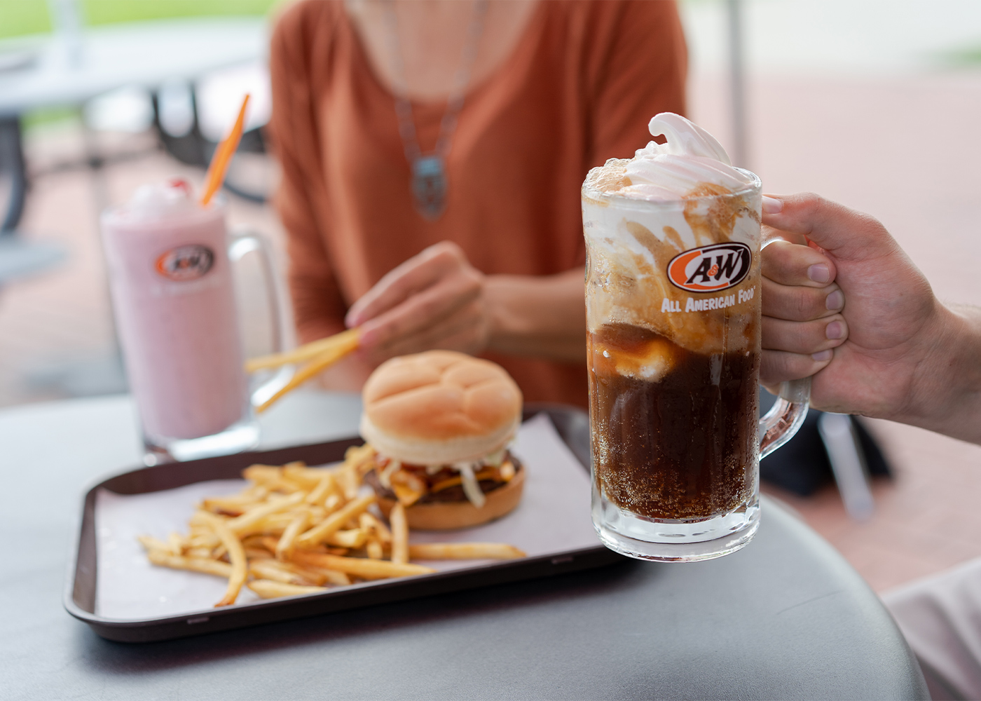 Photo of two people sitting at a table. Person in the foreground is holding an A&W Root Beer Float in a frosty mug. Person in background is holding a fry.