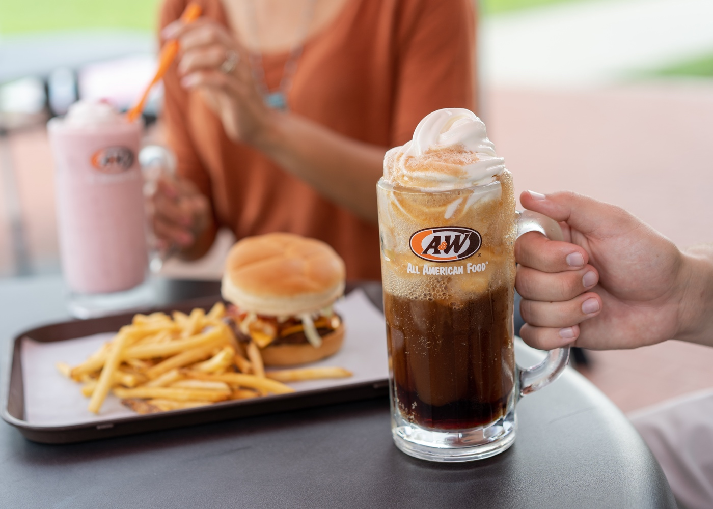 Hand holding an A&W Root Beer Float in a frosty mug.