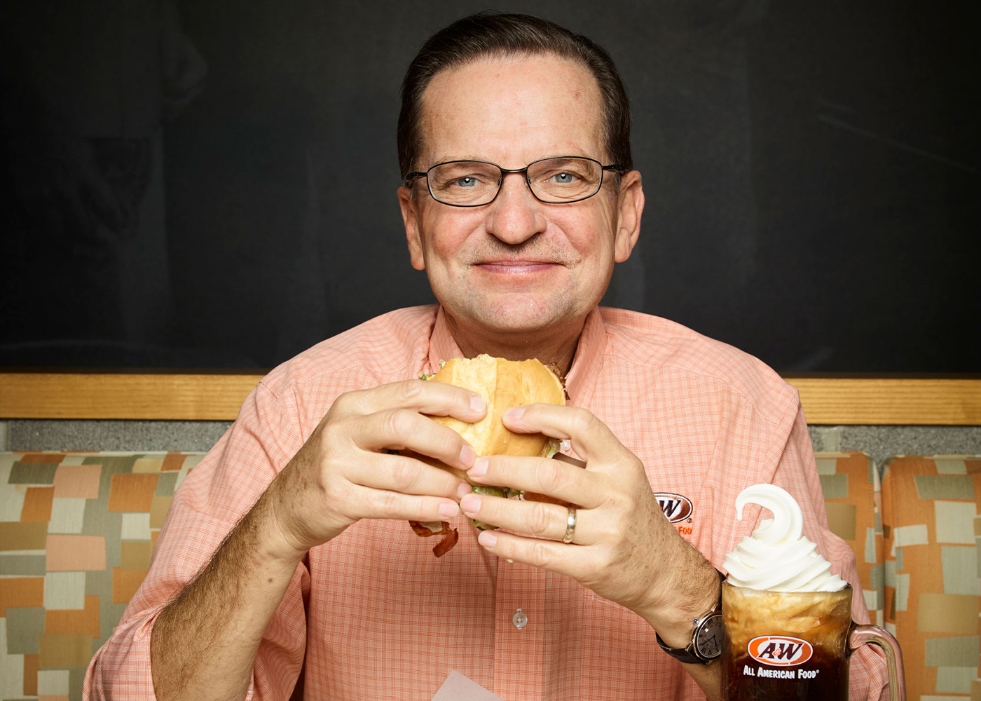 Photo of A&W CEO Kevin Bazner sitting at an A&W booth holding a burger with both hands. A Root Beer Float is on Kevin's left.