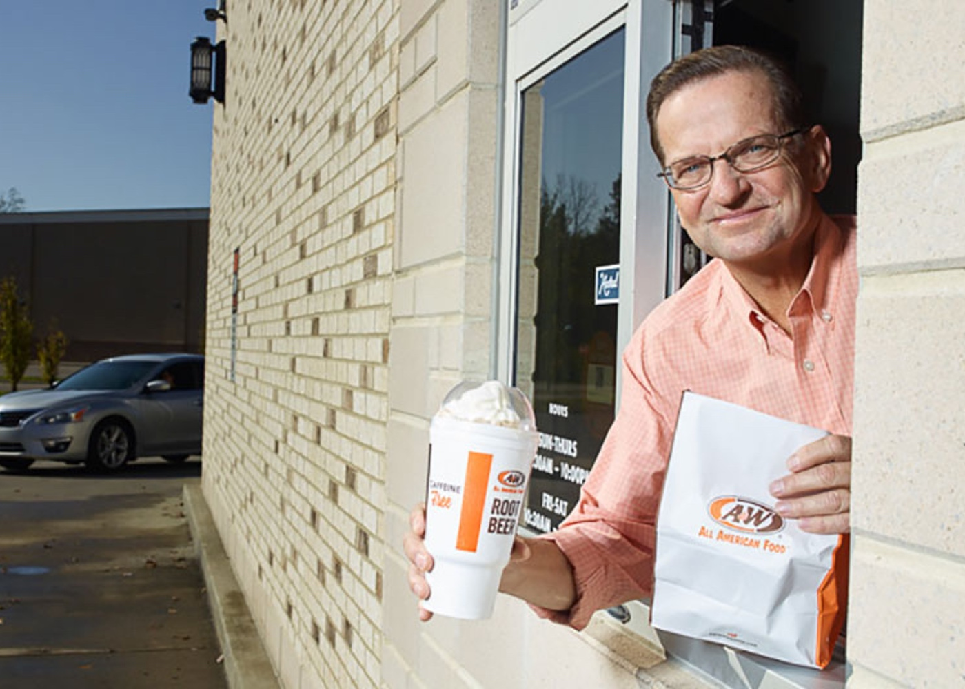 Photo of Kevin Bazner in drive-thru holding Root Beer Float and A&W to-go bag