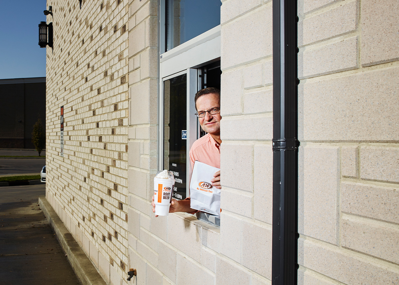 Photo of Kevin Bazner holding an A&W bag and to-go cup in an A&W drive-thru window.
