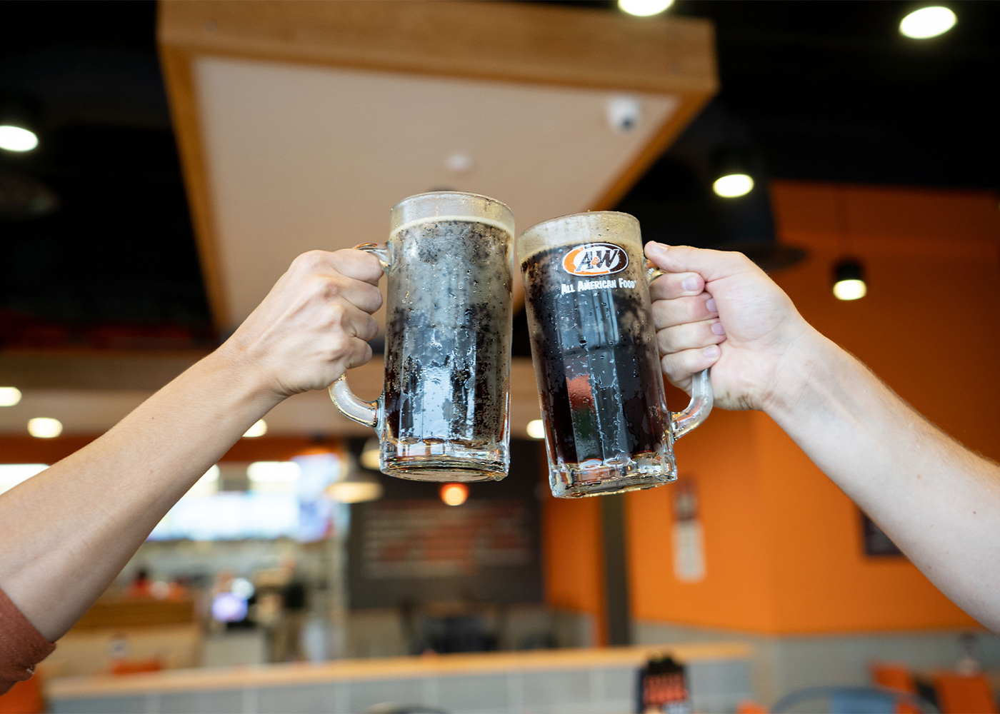 Two people toasting with mugs of A&W Root Beer inside an A&W Restaurant.