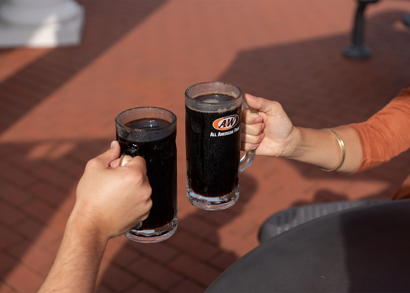 Two people outdoors toasting with mugs of A&W Root Beer