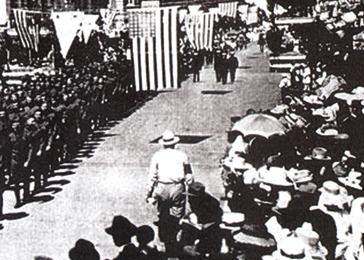black and white photo of parade crowd featuring first A&W Root Beer stand in top righthand corner