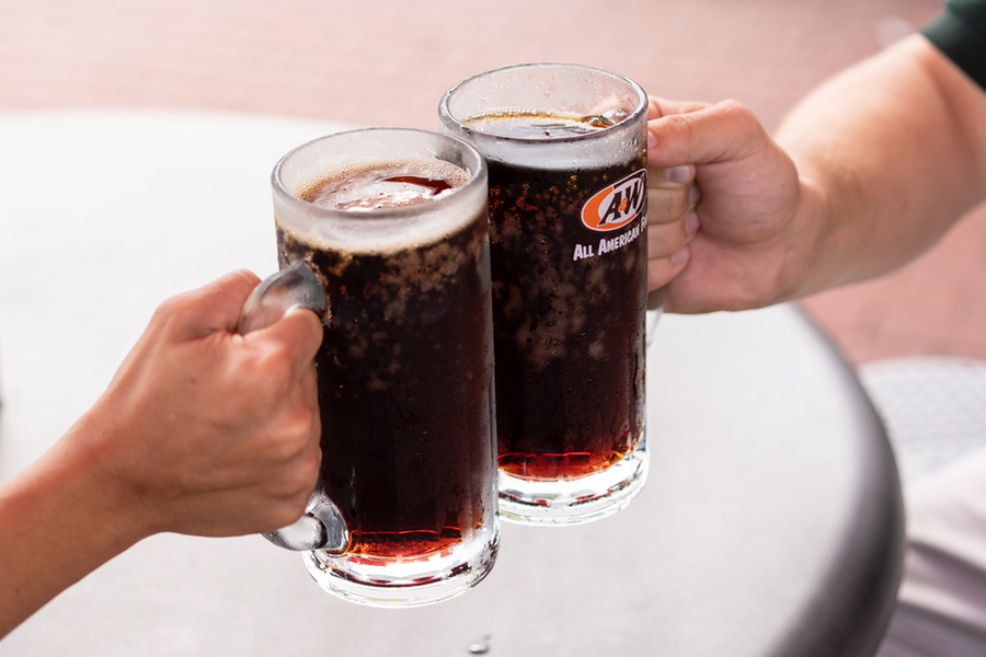 Two people holding mugs of A&W Root Beer together.