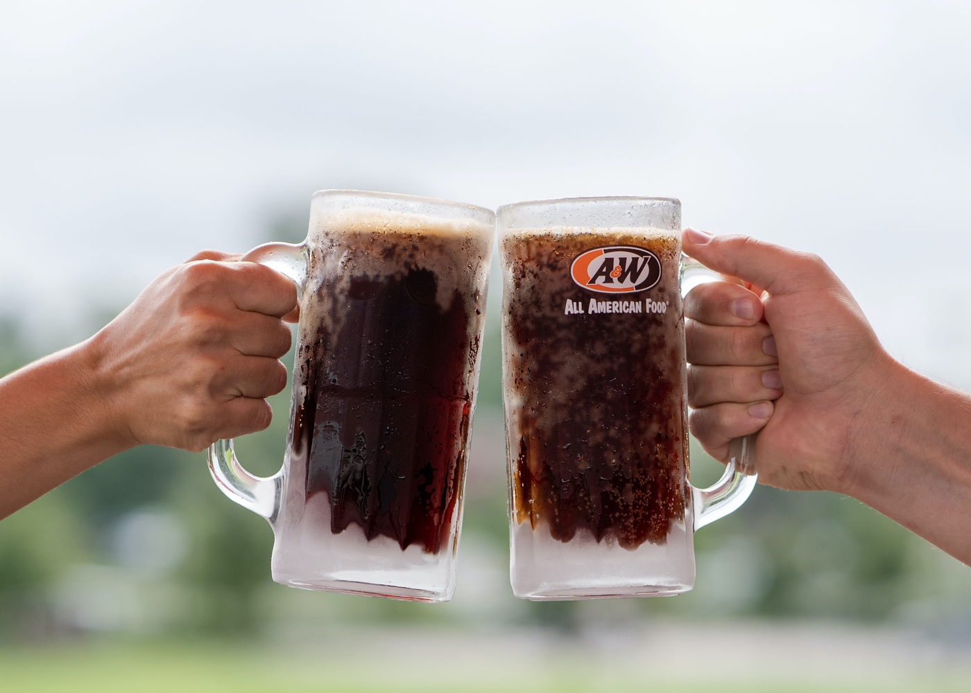 Two people clinking mugs of root beer together.