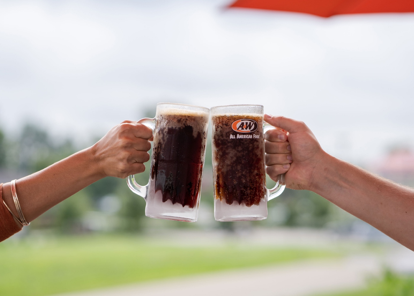 Two people toasting with mugs of A&W Root Beer