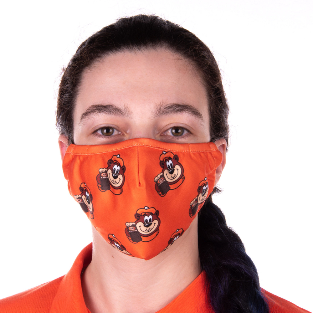 Photo of girl wearing orange face mask featuring icons of Rooty the Great Root Bear