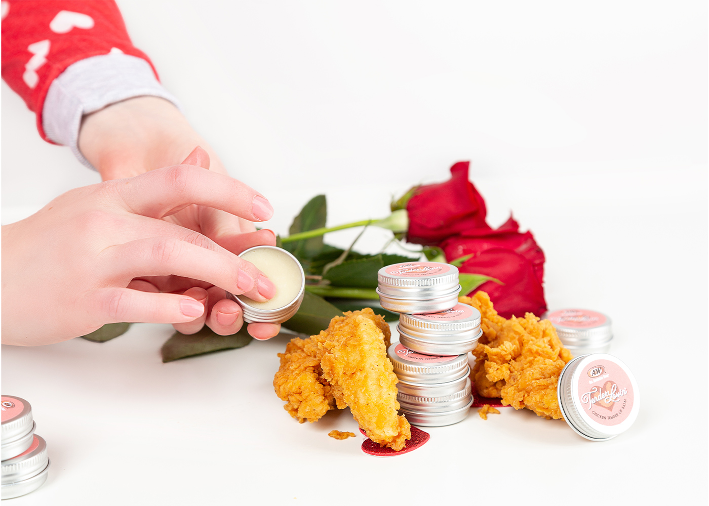 Hand holding tin of Tender Lovin' Lip Balm. Roses and A&W Chicken Tenders are in the background.